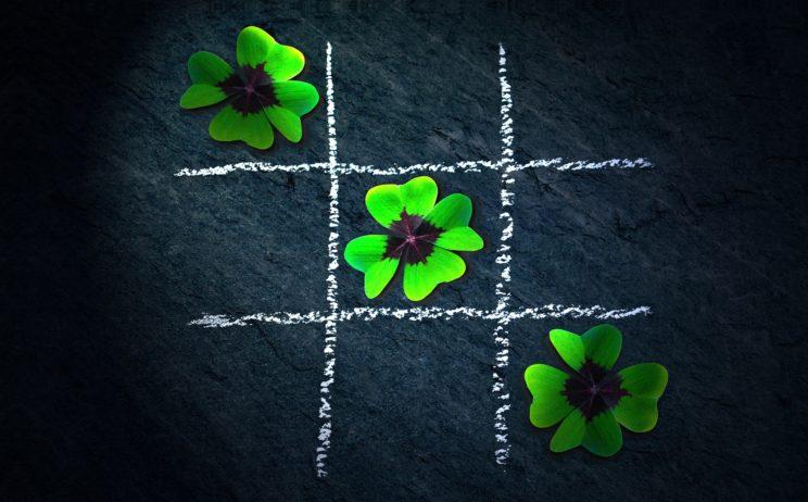 jak dbać o SEO i rozwijać własny biznes; gra kółko i krzyżyk; białe linie, narysowane kredą i ułożone zielone kwiatki 3 pod rząd po skosie